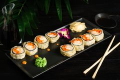 set of sushi rolls on a black plate on a black wooden background with green leaves of a houseplant stock photos