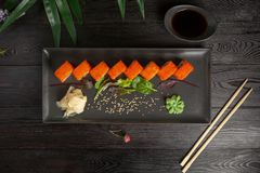 set of sushi rolls on a black plate on a black wooden background with green leaves of a houseplant stock images