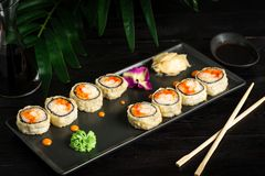 set of sushi rolls on a black plate on a black wooden background with green leaves of a houseplant stock image