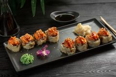 Set of sushi rolls on a black rectangular plate on a black wooden background stock photo