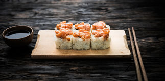 A set of sushi rolls with salmon topping on wooden board Royalty Free Stock Image
