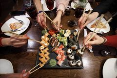 A party of friends eating sushi rolls using bamboo sticks. stock photo
