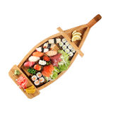 Set of sushi on wooden stand in the form of the boat isolated Stock Image