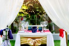 Set the table for dinner with wine romantic style near the pool. On white table have กim light Royalty Free Stock Images