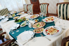 Set the table in the restaurant. Bright interior. Salads and snacks Stock Photo