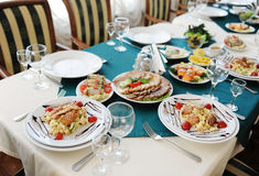 Set the table in the restaurant. Bright interior. Salads and snacks Royalty Free Stock Photos