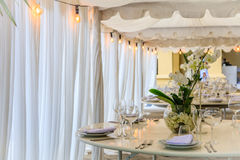 Set table for a white wedding dinner decorated with orchids. Stock Images
