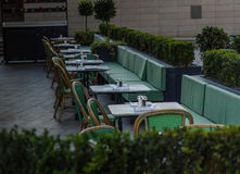 Set tables outside the restaurant waiting for customers, green c Royalty Free Stock Image