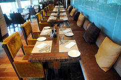 Set tables in restaurant. Row of set tables and benches with cushions in empty restaurant Royalty Free Stock Photos
