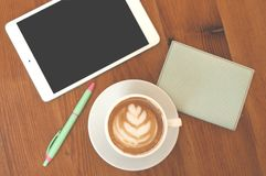 Flat lay of coffee, tablet, pen and notepad. stock photography