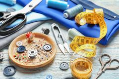 Set of tailoring tools, accessories and fabric on table stock illustration
