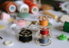 Set of tailoring tools and accessories on table. Multicolored bobbins thread on the background of accessories for sewing close-up Royalty Free Stock Photos