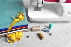 Set of tailoring tools, fabric and sewing machine. On table Royalty Free Stock Images