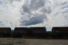 Set of tanks with oil and fuel transport by rail under cloudy sky royalty free stock photo