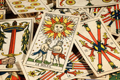 Set of tarot cards. Set of old tarot cards lying in a scattered heap with their designs uppermost and a picture of the sun on top royalty free stock photography