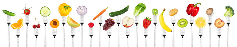 Set of tasty fruits and vegetables on forks Stock Image