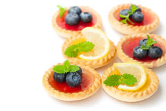 Set  of tasty tartlets  with lemon and raspberry jam isolated. Set  of tasty tartlets with lemon and raspberry jam isolated Royalty Free Stock Image