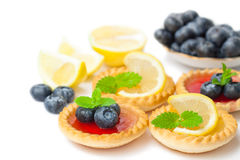 Set  of tasty tartlets with lemon and raspberry jam isolated. Set of tasty tartlets with lemon and raspberry jam isolated Stock Images