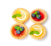 Set  of tasty tartlets  with lemon and raspberry jam isolated. Set  of tasty tartlets with lemon and raspberry jam isolated Royalty Free Stock Photo