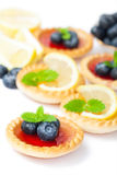 Set  of tasty tartlets with lemon and raspberry jam isolated. Set  of tasty tartlets  with lemon and raspberry jam isolated Stock Photos