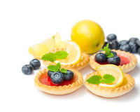 Set  of tasty tartlets with  lemon and raspberry jam isolated. Set  of tasty tartlets with lemon and raspberry jam isolated Royalty Free Stock Photos
