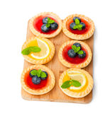 Set  of tasty  tartlets with lemon and raspberry jam on wooden bo. Set  of tasty tartlets with lemon and raspberry jam on wooden board isolated Stock Images