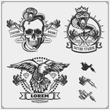 Set of tattoo salon labels, badges and design elements. Tattoo studio emblems with professional equipment, skull, eagle and cobra. royalty free illustration