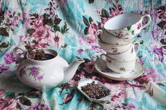 Set for tea with black tea with heather. Kettle, set different cups, tea with flowers of heather on fabric background with floral pattern Royalty Free Stock Image