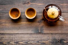 Set for tea ceremony. Glass teapot and ceramic cups on dark wooden background top view copyspace Royalty Free Stock Photos