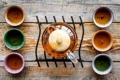 set tea för ceremoni Glass tekanna och keramiska koppar på bästa sikt för lantlig träbakgrund Royaltyfria Bilder