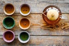 set tea för ceremoni Glass tekanna och keramiska koppar på bästa sikt för lantlig träbakgrund Royaltyfri Fotografi
