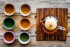 set tea för ceremoni Glass tekanna och keramiska koppar på bästa sikt för lantlig träbakgrund Royaltyfri Bild