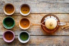 set tea för ceremoni Glass tekanna och keramiska koppar på bästa sikt för lantlig träbakgrund Arkivbilder