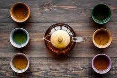 set tea för ceremoni Glass tekanna och keramiska koppar på bästa sikt för mörk träbakgrund Fotografering för Bildbyråer