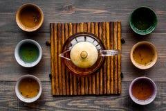 set tea för ceremoni Glass tekanna och keramiska koppar på bästa sikt för mörk träbakgrund Arkivfoto