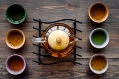 set tea för ceremoni Glass tekanna och keramiska koppar på bästa sikt för mörk träbakgrund Arkivbild