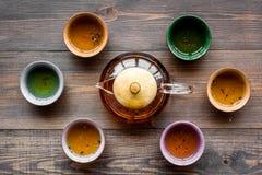 set tea för ceremoni Glass tekanna och keramiska koppar på bästa sikt för mörk träbakgrund Royaltyfria Bilder