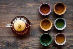 set tea för ceremoni Glass tekanna och keramiska koppar på bästa sikt för mörk träbakgrund Royaltyfria Foton