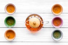 set tea för ceremoni Glass tekanna och keramiska koppar på bästa sikt för vit träbakgrund Royaltyfri Foto