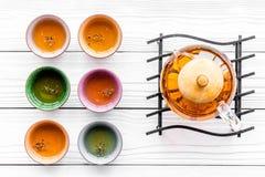 set tea för ceremoni Glass tekanna och keramiska koppar på bästa sikt för vit träbakgrund Arkivbilder