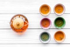 set tea för ceremoni Glass tekanna och keramiska koppar på bästa sikt för vit träbakgrund Fotografering för Bildbyråer