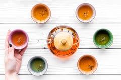set tea för ceremoni Glass tekanna och keramiska koppar på bästa sikt för vit träbakgrund Royaltyfria Bilder