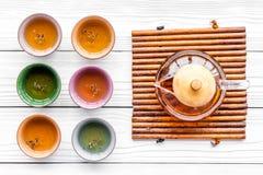set tea för ceremoni Glass tekanna och keramiska koppar på bästa sikt för vit träbakgrund Royaltyfri Fotografi