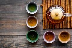 set tea för ceremoni Glass tekanna och keramiska koppar på mörk träcopyspace för bästa sikt för bakgrund Royaltyfri Bild