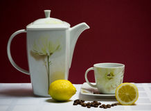 Set of tea-pot, cup and saucer on maroon Stock Photography
