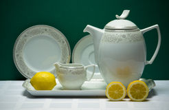 Set of tea-pot, milk jug and saucers with lemons Royalty Free Stock Image