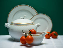 Set of tea-pot, milk jug and saucers with tomatoes Royalty Free Stock Photos