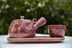 A set of tea pot on a white table. A beautiful, set of purple ceramic chinese style tea pot and tea cup on white table. garden background japanese teapot royalty free stock photography
