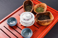 Set of teapot, three kinds of tea and four bowls Royalty Free Stock Photography