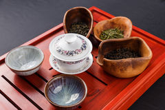 Set of teapot, three kinds of tea and four bowls Royalty Free Stock Image